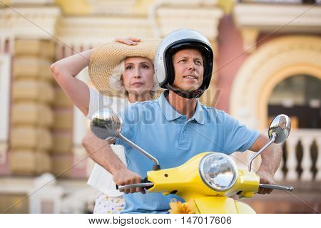 Man with woman on scooter. Guy in a helmet. Must overcome long way. Risky tourists choose a path.