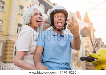 Adult couple showing tongues. Man with phone beside woman. We rode on a tour. Serious faces aren't in fashion.