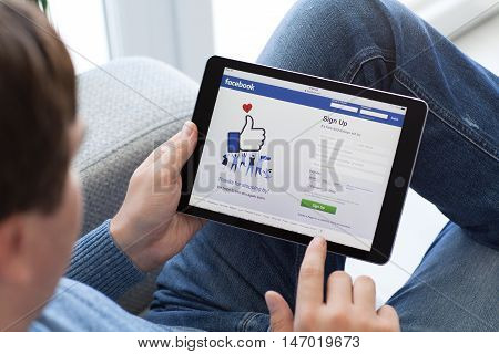 Alushta Russia - September 2 2016: Man holding a iPad Pro Space Gray with social networking service Facebook on the screen. iPad Pro was created and developed by the Apple inc.