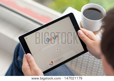 Alushta Russia - June 5 2016: Man holding a iPad Pro Space Gray with social networking service Google on the screen. iPad Pro was created and developed by the Apple inc.
