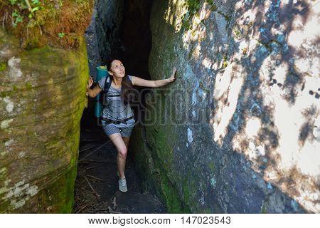 Woman Hiker Backpacker exploring narrow canyon in summer day.