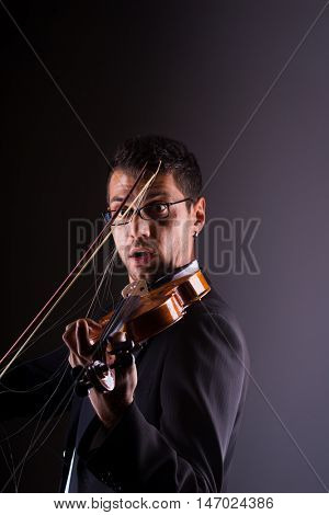 Violinist  playing a broken  violin on dark background,