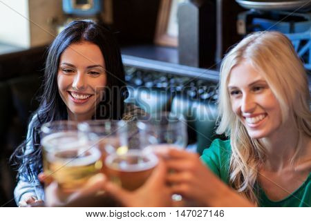 people, leisure, friendship and celebration concept - happy women drinking beer with friends and clinking glasses at bar or pub