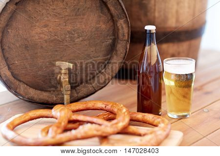 brewery, drinks and alcohol concept - close up of old beer barrel, glass, bottle and pretzel on wooden table