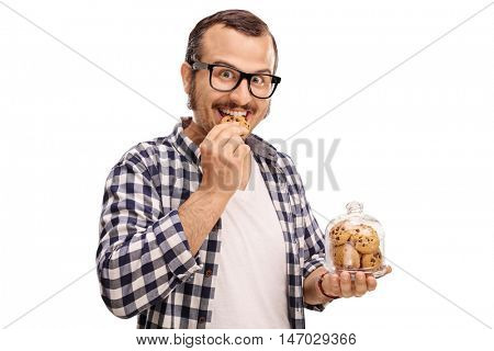 Smiling man eating a cookie and holding a jar full of cookies isolated on white background