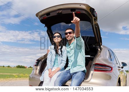 travel, summer vacation, road trip, leisure and people concept - happy couple hugging at open trunk of hatchback car and pointing finger outdoors