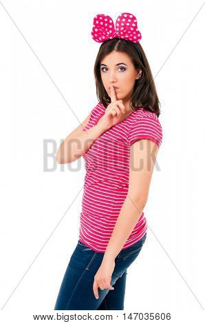 Portrait of a pretty girl teenager making silence gesture, isolated white background. Young beautiful woman with finger on lips show secret sign.