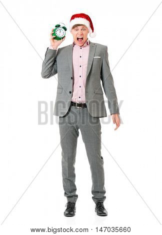 Caucasian man wearing christmas hat for santa. Young businessman in gray suit with alarm clock isolated on white background. Successful boy wearing Santa Claus hat - full lenght portrait.
