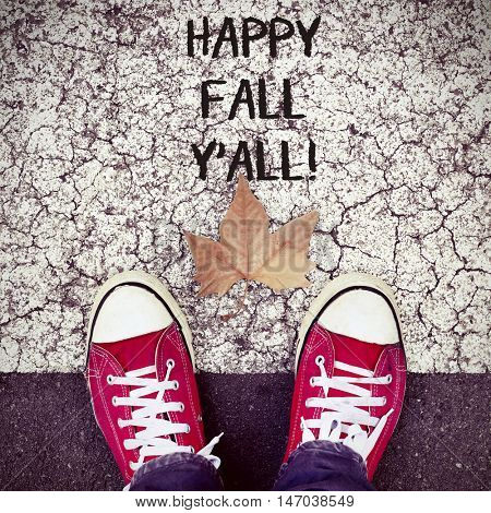 high-angle shot of a dry leaf and the feet of a man wearing red sneakers on the asphalt, and the text happy fall yall