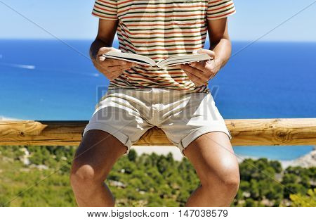 closeup of a young caucasian man wearing cut-offs reading a book with the sea in the background