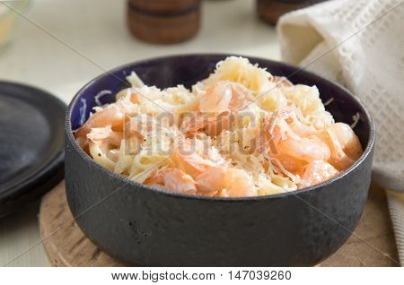 Pasta with shrimps fettucine olive oil cream cheese parmesan and spices in pan