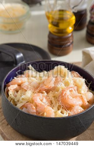 Pasta with shrimps fettucine oil cream cheese parmesan and spices in frying pan