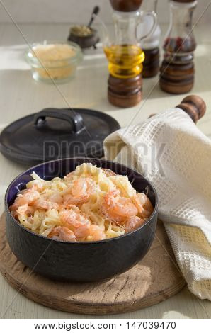 Pasta with shrimps fettucine oil cream and cheese parmesan spices in baking pan