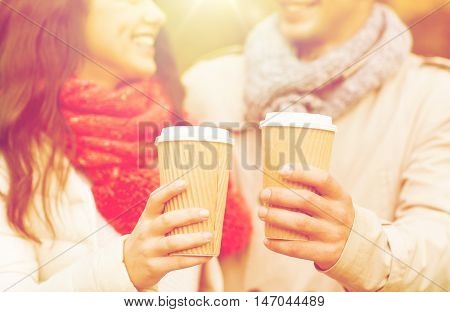 love, season, drinks and people concept - close up of happy smiling couple with coffee cups in autumn park