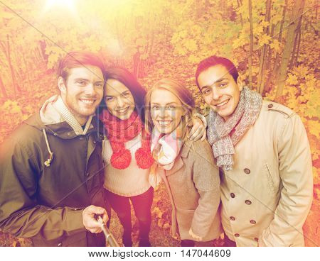 season, people, technology and friendship concept - group of smiling friends with smartphone or digital camera and selfie stick taking picture in autumn park
