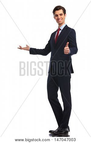 full body picture of a  young business man presenting and making the ok thumbs up hand sign, isolated on white background