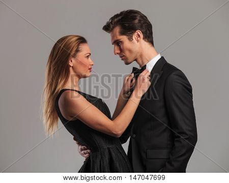 elegant sexy woman fixing her lover's bowtie in studio