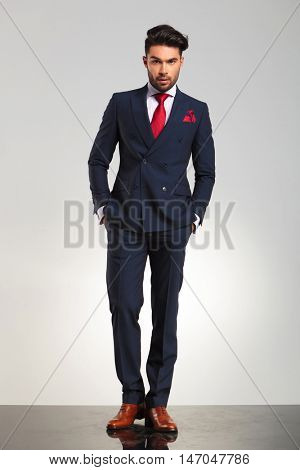 elegant business man in double breasted suit standing with hands in pockets on grey studio background