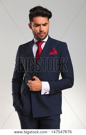 arrogant young business man looking to side while holding a button on his suit on grey background