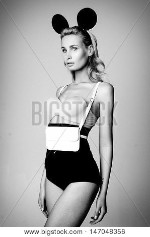 Young attractive woman wearing high waist lingerie with leather black sword belt bag and mouse ears, black and white photo