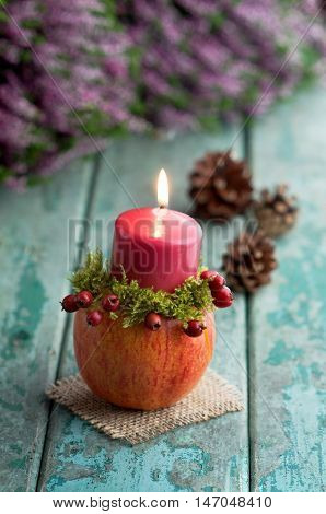 Autumnal decoration with candleholder on turquoise wood