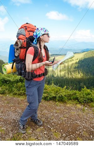 Woman tourist in mountain determines the direction with a compass and map. Hiker watching the map. Girl tourist with map and compass. Lifestyle concept active leisure tourism. Hiking poster