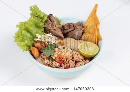 Noodle with tom yam topped with minced pork,chicken liver,wonton,shrimp ,chili. and green lemon on white background.