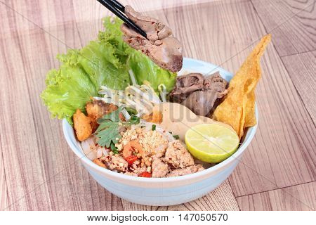 Noodle with tom yam topped with minced pork,chicken liver,wonton,shrimp ,chili. and green lemon on wood.