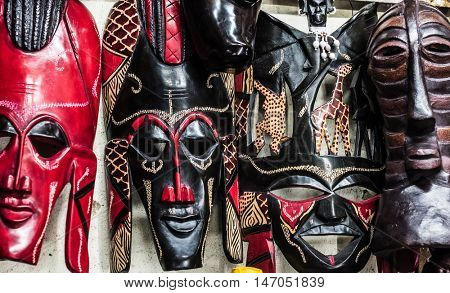 different colorful tribal wooden masks at african souvenir market