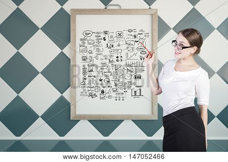 Young businesswoman giving presentation on business with sketch in picture frame. Chessboard wall background. Success concept