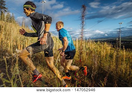 Revda Russia - September 10 2016: two men runners skyrunners running uphill trail in grass on blue sky background during marathon Vertical kilometer
