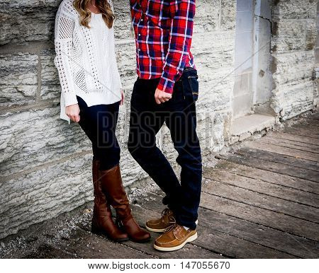 Image of engaged couple against stone wall and on woodent path.