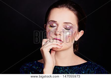 Glamorous Woman with Glitters Makeup. Beautiful Face on Black Background