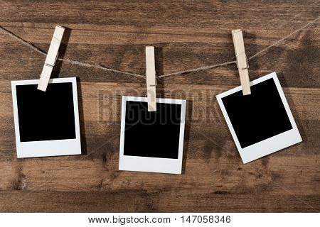 Three Blank Polaroid Frames Hanging on Twine Attached with Clothespins on Wooden Background