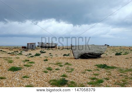 An overcast day,  Dungeness, Kent, with abandoned buildings and boats.