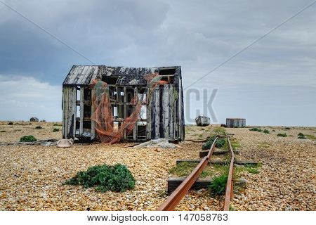 An overcast day,  Dungeness, Kent, with abandoned buildings, rail tracks and boats.