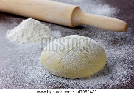 Dough for pizza or bread with rolling pin and flour on a stone surface.
