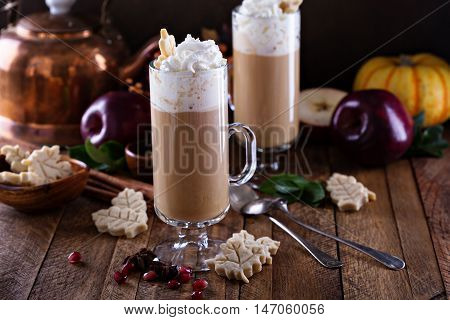 Apple cider latte with spices and whipped cream, hot seasonal fall drink