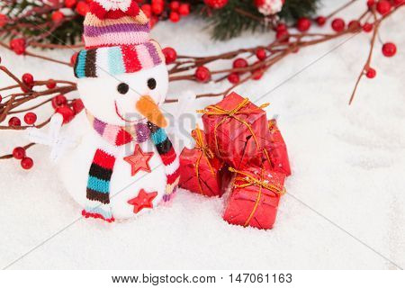 Snowman made of wool over the snow with a branch of red berries background. Christmas decoration