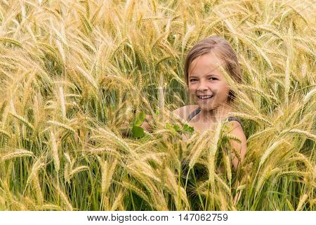 Smiling young girl on a wheat field smiling