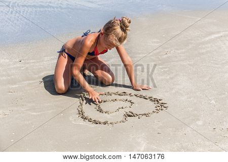 Love the sea - little girl drawing heart shape in the sand on the sea shore - copy space