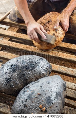 Making bread the traditional way - cleaning the charred crust from an oven baked bread closeup