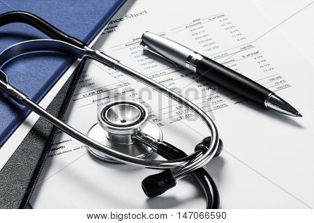 Pen And Stethoscope On Financial Report Close-up