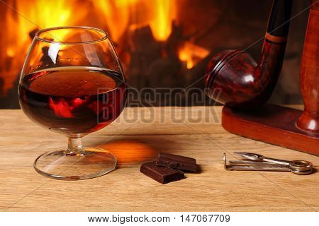A glass of brandy chocolate and tobacco pipe on oak table on the background of a burning fireplace