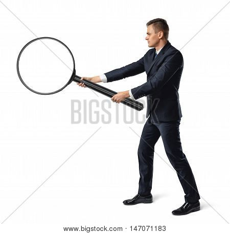 Side view of a businessman holding big magnifier with both hands isolated on white background. Enlarging objects. Searching and analyzing. Investigation.