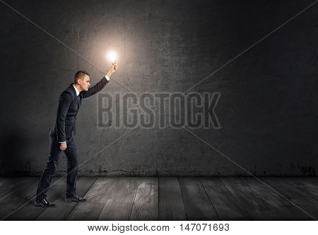 Side view of a businessman with glowing light bulb in outstretched arm going through darkness. Solving problems. Looking for ideas. Brainstorming.