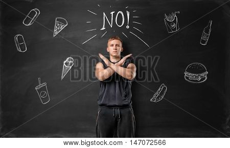 Muscled young man showing stop sign with his hands and says no to unhealthy food on the background of blackboard. Healthy lifestyle. Sportive nourishment.