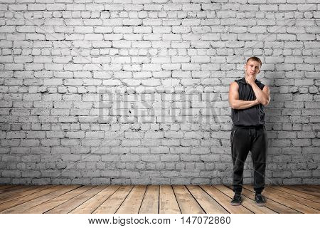 Front view of muscled young man standing with hand on his chin looking thoughtfully on the background of white brick wall. Wellbeing. Muscleman. Workout and fitness.