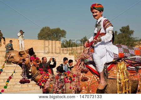 JAISALMER. INDIA - FEB 1, 2015: Young camel rider in colorful dress goes past the tourist crowd of popular Desert Festival on February 1, 2015 in Rajasthan. Every winter Jaisalmer takes the Desert Festival