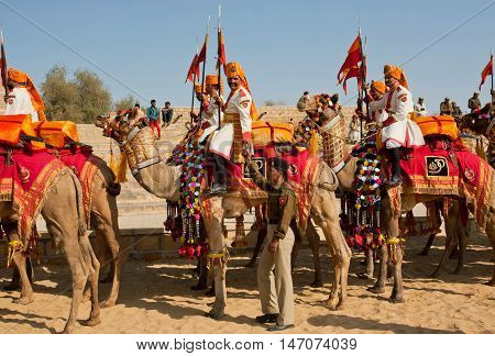 JAISALMER, INDIA - Feb 1, 2015: Camel riders in indian military uniform going to traditional rural show of the Desert Festival on February 1, 2015 in Rajasthan. Every winter Jaisalmer takes the Desert Festival